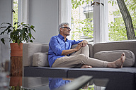 Mature man sitting on couch at home - RBF05942