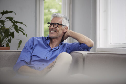 Portrait of laughing mature man sitting on couch at home - RBF05945