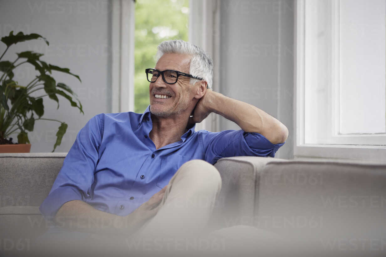 Portrait of laughing mature man sitting on couch at home - RBF05945 - Rainer Berg/Westend61