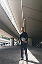 Businessman standing at underpass holding laptop - KNSF02473
