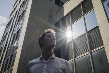 Businessman standing outdoors with sun reflecting in office building - KNSF02479