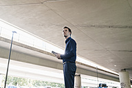 Businessman standing at underpass holding tablet - KNSF02485