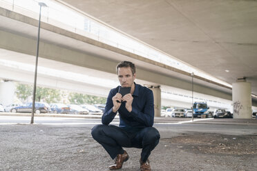 Businessman crouching at underpass holding tablet - KNSF02488