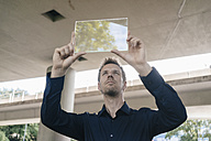 Businessman holding up portable glass device - KNSF02491