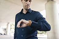 Businessman standing at underpass checking the time - KNSF02494