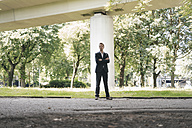 Businessman standing outdoors at a bridge - KNSF02500