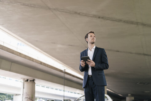 Businessman standing at underpass holding tablet - KNSF02503