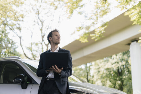 Businessman standing next to car using laptop - KNSF02506