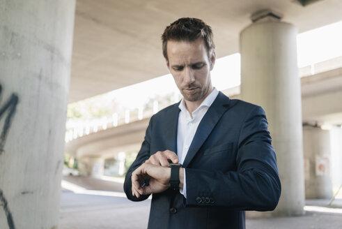 Businessman standing at underpass using smartwatch - KNSF02509