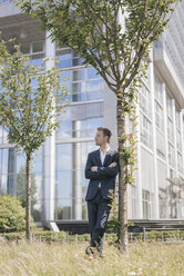 Businessman leaning against a tree in front of office building - KNSF02518