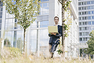Businessman leaning against a tree in front of office building using laptop - KNSF02524
