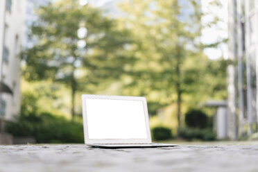 Laptop on cobblestones in park with office buildings in background - KNSF02533