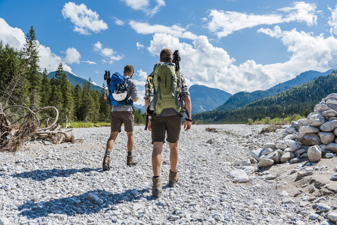 Germany, Bavaria, back view of two hikers walking in dry creek bed - DIGF02780