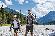 Germany, Bavaria, two hikers walking in dry creek bed - DIGF02783