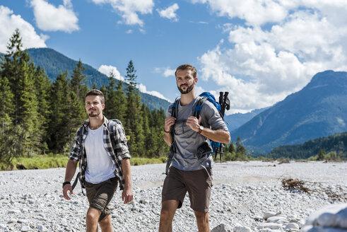 Germany, Bavaria, two hikers walking in dry creek bed - DIGF02783