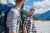 Germany, Bavaria, portrait of young hiker with backpack looking at his friend - DIGF02786