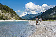 Germany, Bavaria, two hikers walking at riverside - DIGF02801
