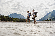 Germany, Bavaria, two hikers with backpacks crossing Isar River - DIGF02804