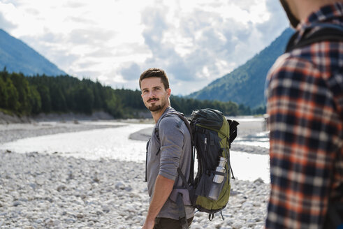 Germany, Bavaria, portrait of young hiker with backpack looking at his friend - DIGF02813