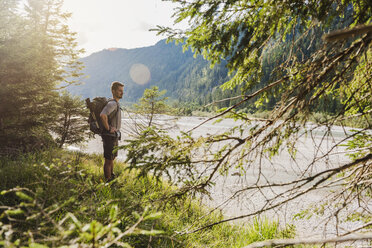 Germany, Bavaria, young hiker with backpack looking at view - DIGF02816