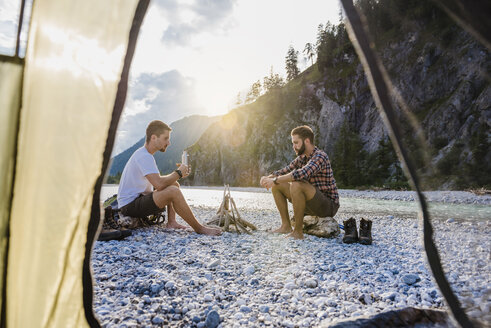 Germany, Bavaria, two hikers camping on gravel bank in the evening - DIGF02831