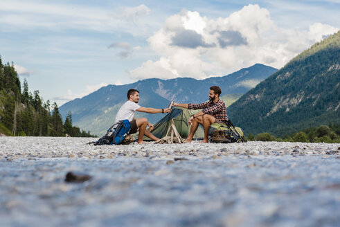Germany, Bavaria, two hikers camping on gravel bank - DIGF02834