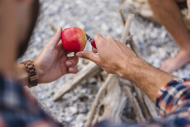 Man's hand cutting apple at camp fire - DIGF02837