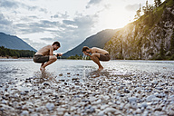 Germany, Bavaria, two friends washing their faces at riverside - DIGF02843