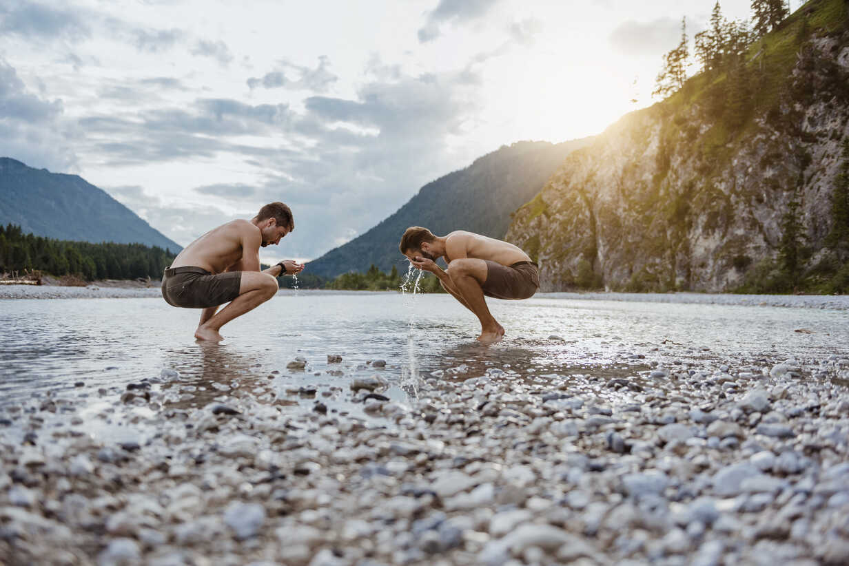 Germany, Bavaria, two friends washing their faces at riverside - DIGF02843 - Daniel Ingold/Westend61