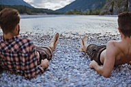 Germany, Bavaria, back view of two friends lying at riverside looking at view - DIGF02846