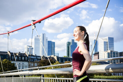 Germany, Frankfurt, sportive young woman standing on bridge - PUF00694