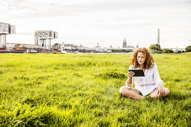 Germany, Cologne, young woman sitting on meadow looking at tablet - FMKF04384