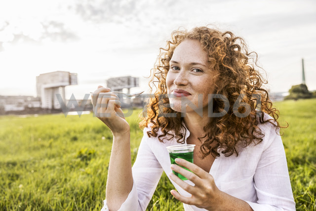 Germany, Cologne, portrait of happy young woman eating jelly on meadow - FMKF04387