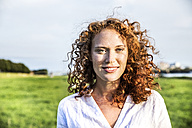Portrait of freckled young woman with curly red hair - FMKF04390