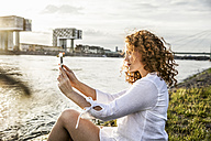 Germany, Cologne, young woman sitting at riverside in the evening taking selfie with cell phone - FMKF04393