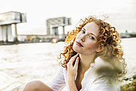Germany, Cologne, portrait of freckled young woman with curly red hair - FMKF04399