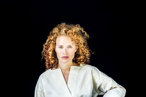 Portrait of serious young woman with curly red hair in front of black background - FMKF04402