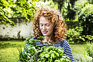 Portrait of young woman with fresh herbs in garden - FMKF04405