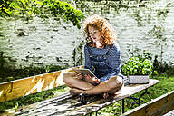Portrait of young woman sitting on beer table in the garden using tablet - FMKF04414
