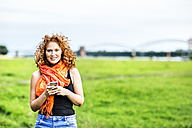 Portrait of smiling young woman with curly red hair on a meadow - FMKF04417