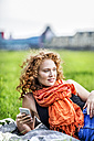 Portrait of smiling young woman with curly red hair wearing orange scarf lying on blanket on a meadow - FMKF04420