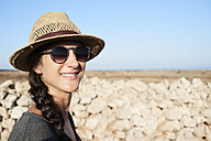 Spain, Menorca, portrait of smiling woman wearing straw hat and sunglasses - IGGF00147