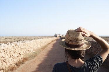 Spain, Menorca, back view of single traveller wearing straw hat - IGGF00150
