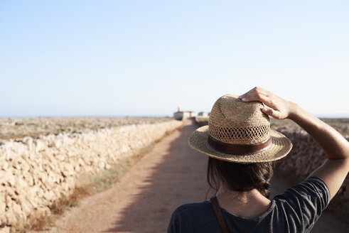 Spain, Menorca, back view of single traveller wearing straw hat - IGGF00150