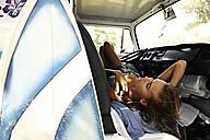 Woman with surfboard lying in van - ECPF00074