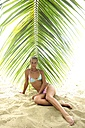 Beautiful young woman sitting under palm tree on the beach - ECPF00098