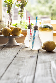 Homemade lemonade with mint on wooden table in front of window - SBDF03299