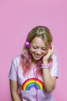 Portrait of young woman listening to music with headphones in front of pink background - MGIF00098
