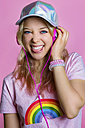Portrait of young woman listening to music with headphones in front of pink background sticking out tongue - MGIF00101
