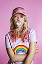 Portrait of cool young woman with bubble gum in front of pink background - MGIF00107